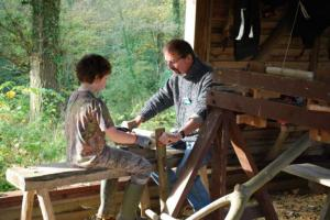 Volunteer Nick Bertenshaw demonstrating how to use the shave horse